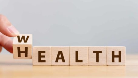 Hand flip wooden cube with word wealth to health. Investment in life insurance and healthcare concept
