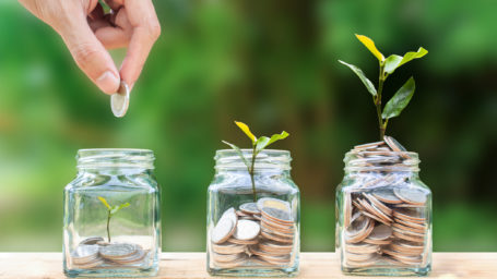 A man hand holding coin over stacked coins in glass jar and growing tree plant depicts Fund growth and wealth.
