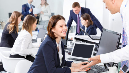 Friendly cheerful positive coworkers having pleasant fun conversation at workplace in modern office