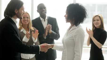Grateful boss shaking hands with African American businesswoman while colleagues applauding